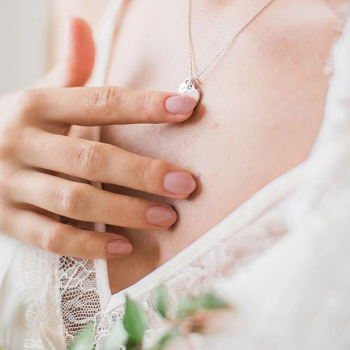 Woman touching hand to heart-shaped necklace
